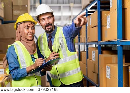 White caucasian warehouse manager command and assign job to muslim asian warehouse worker in distribution center. For business warehouse inventory and logistic concept.