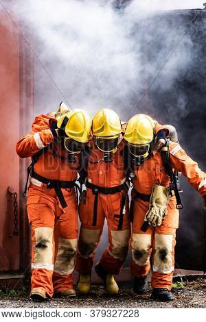 Asian firefighters rescue their team colleague from from burning building. Firefighter safety rescue from accident and public service concept.