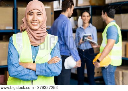 Portrait of Islam Muslim female warehouse worker crossed arm with her colleagues meeting in warehouse distribution center environment. For business warehouse inventory and logistic concept.
