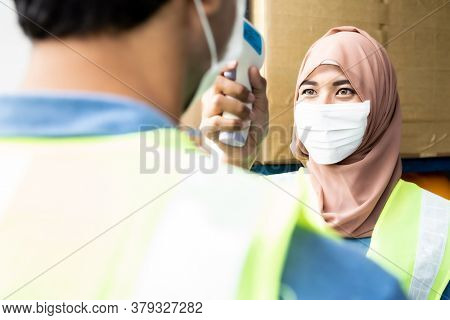 Islam asian warehouse worker take temperature to worker before getting in factory after reopening after city lockdown from COVID-19 coronavirus pandemic in warehouse distribution center environment.