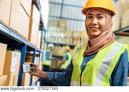 Portrait of Islam Muslim female warehouse worker use mobile phone scan qr code for online inventory in warehouse distribution environment. Using in business warehouse technology and logistic concept.