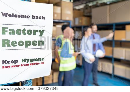 Factory reopen signage with warehouse manager and worker meeting in background after city lockdown from COVID-19 coronavirus pandemic in warehouse distribution center environment.