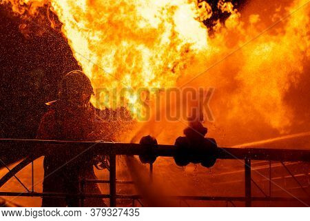 Firefighter using water fog type fire extinguisher to fighting with the fire flame from oil pipeline leak and explosion. Firefighter and industrial safety concept.