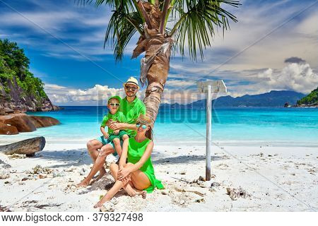 Family on beautiful Petite Anse beach, young couple with three year old toddler boy sitting on palm tree. Summer vacation at Seychelles, Mahe.