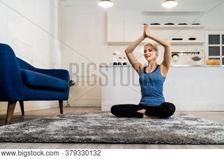 White caucasian fit sporty woman doing yoga Sukhasana sit pose in living room at home for mental health and meditation. Working out, fitness sport and healthy lifestyle concept.