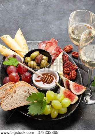 Antipasto plate with prosciutto, cheese, figs and grapes. Appetizer board. With copy space