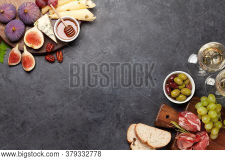 Antipasto plate with prosciutto, cheese, figs and grapes. Appetizer board and white wine. Top view flat lay with copy space