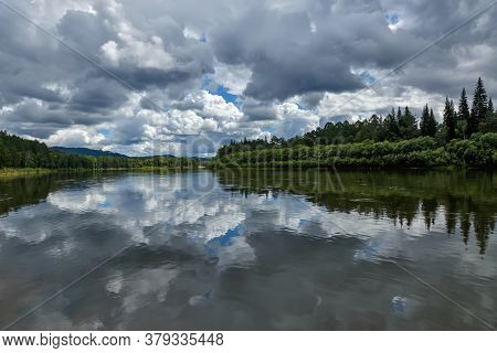 A Natural Landscape With Clouds Reflecting On The Surface Of A Calm River With Green Forest On Its B
