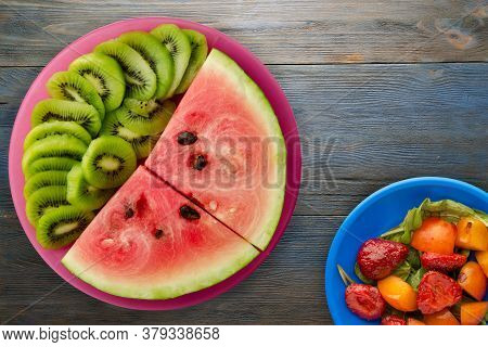 Watermelon And Kiwi Sliced On A Red Plate With Fruits Salad On A Blue Gray Wooden Background Top Vie
