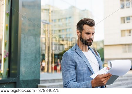 Concentrated serious young unshaved handsome business man outdoors at the street near business center holding documents