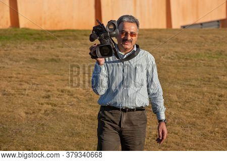 Iranian cameraman carries a video camera in a bright sunny day