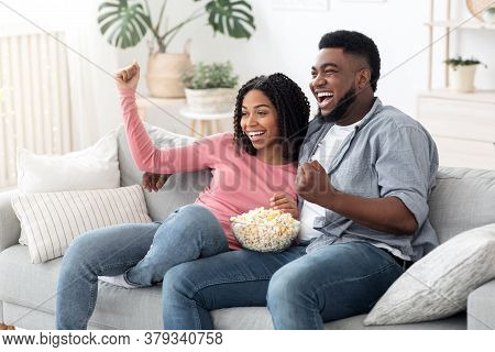 Couple Leisure. Happy Black Spouses Watching Tv And Cheering Sports, Eating Popcorn And Relaxing On