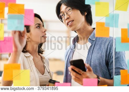 Image of young multinational pleased colleagues using mobile phone and talking while working in office