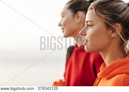 Image of young beautiful gorgeous girls friends walking outdoors looking aside.