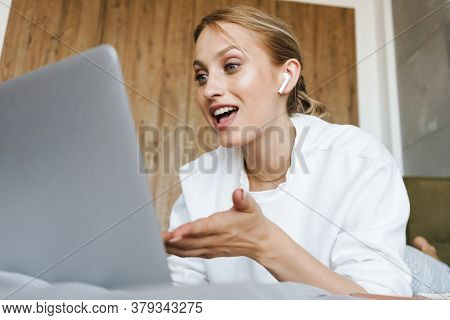 Image of a young cute woman in a bedroom indoors at home talking by videocall by laptop computer