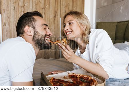 Image of a young smiling optimistic loving couple relaxing on a bed in bedroom indoors at home while eating pizza