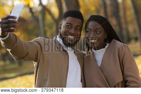 Happy Young Black Man And Woman Taking Self-portrait During Walking In Autumn Park