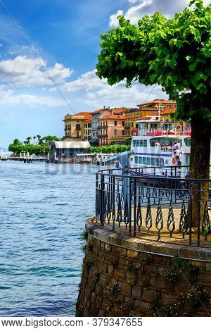 Como lake Bellagio town in Lombardy, Milan, Italy, Tree at embankment. Water transport boat with passengers. Beautiful architecture italian houses.