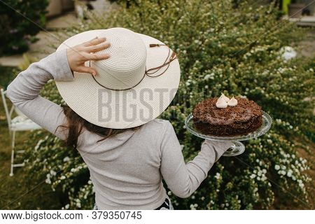 Picture Is From Behind. Girl Holding Her White Hat And Chocolate Cake On Plate With Standing With Fo