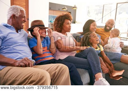 Multi-Generation African American Family Relaxing At Home Sitting On Sofa Watching TV Together