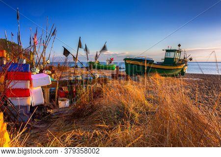 Fishing boats on the Baltic Sea beach at sunrise in Gdynia Orlowo, Poland