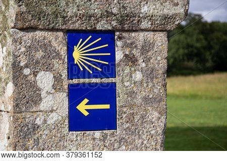 Camino De Santiago Yellow Scallop And Arrow Sign On Old Stone Wall. Way Of St. James Signs Pilgrimag
