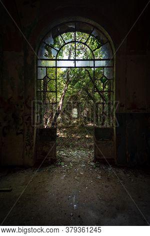 Arched Door With Broken Windows In An Old Dilapidated Italian Building Of The Twentieth Century, Urb
