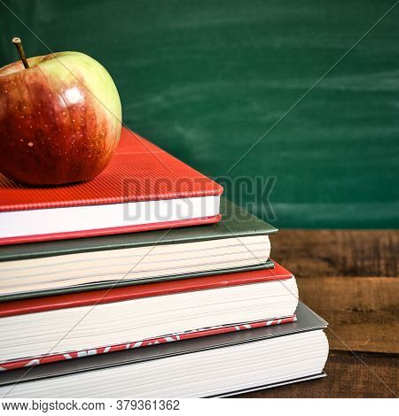 Books And Apple On Wooden Table In Front Of The School Chalkboard. Back To School Concept. Vintage T