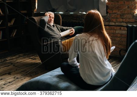 Professional Mature Man Psychologist Consulting Female Patient At Psychological Appointment In Dark