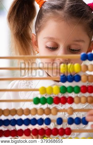 Small girl with abacus in the classroom