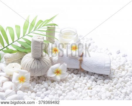 Spa setting with frangipani , candle , herbal ,ball,cream,green palm leaves ,rolled towel on pile of white stones