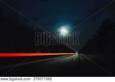 Light Trails From Vehicles Traveling On Rural Road, Surrounded By Two Rows Of Trees, Late At Night W