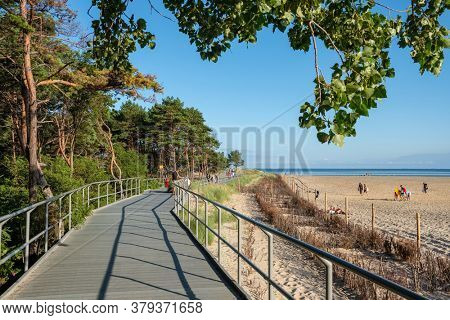 Sopot, Poland - July 24, 2019: Wooden path at Sandy Baltic coast with pine trees. Sand beach at Baltic sea in Poland