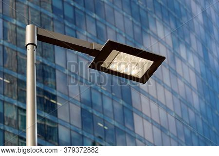 Led Street Lamp Post Glowing On Skyscraper Background. Modern Led Lights In City, Saving Of Electric