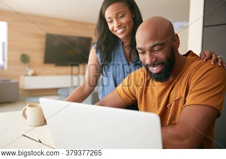 African American Couple Using Laptop To Check Finances At Home