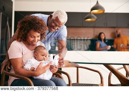 Grandparents Cuddling Baby Granddaughter At Home With Parents In Background