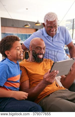 Multi-Generation Male African American Family Sitting On Sofa At Home Using Digital Tablet