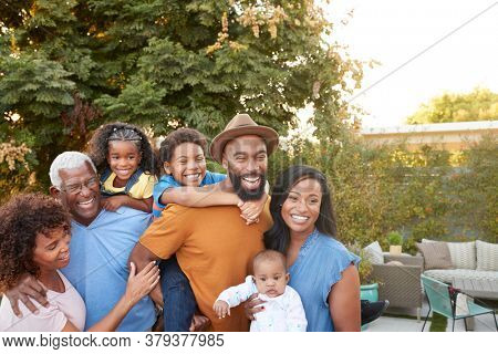 Portrait Of Multi-Generation African American Family Relaxing In Garden At Home Together