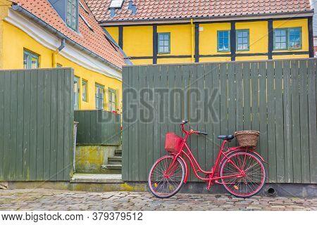 Red Bicycle Against A Green Fence In The Old Part Of Ribe, Denmark