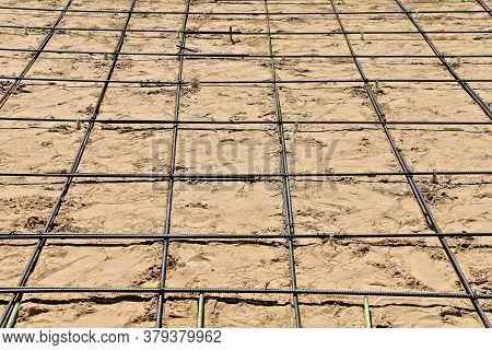 Criss-crossing Reinforcing Bars Made A Grid Pattern Of Squares Over Sand On A Future Driveway Site T