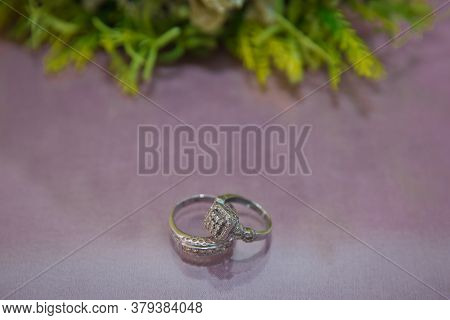 Bride And Groom With Engagement Gold Rings Put On The Table, And Next To Them Lies A Wedding Bouquet