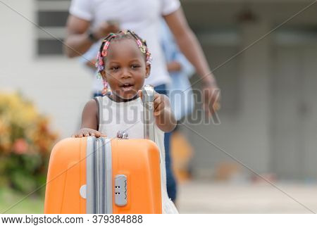 Travel Concepts, Orange Luggage With Blurred Cheerful African American Girl And Parent Family Leavin