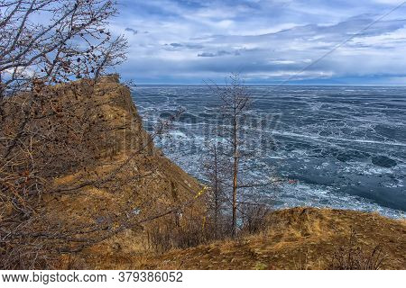 Baikal Lake In The May Ice Drift. Island Of Olkhon And The Movement Of White Ice On The Blue Water
