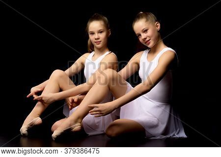Two Charming Gymnasts In Beautiful Sports Swimsuits Posing In The Studio. The Concept Of Childrens S