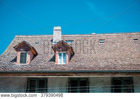 House With A Tiled Roof Against A Clear Blue Sky.