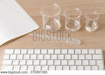 Glass Measuring Beakers Standing Gradually On Table And Plastic Pipette In Front Of A White Computer