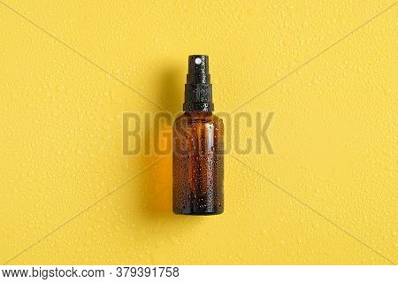 Wet Amber Glass Spray Bottle Mockup With Water Drops On Yellow Background, View From Above. Suntan L