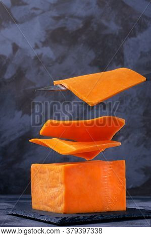 Levitating Slices Of Red Cheddar Cheese Against The Grey Background. Flying Food