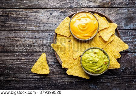 Nachos Chips In A Bowl With Sauces Guacamole And Cheese, Dip Variety, Over Dark Wooden Background, T