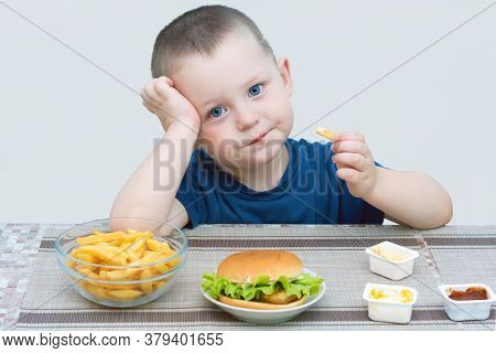 Little Blue-eyed Boy Eating Fast Food. On A Light Background, The Child Is Sad, Does Not Smile. Conc
